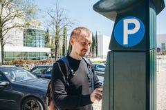 Un hombre paga parquear usando una máquina especial a la paga en Lisboa en Portugal fotos de archivo