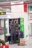 Un hombre para añadir artículos a la máquina expendedora Fotos de archivo