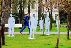 Un hombre pasa a través del parque entre las siluetas que representan a las víctimas del tráfico y de la indiferencia en el teléf Fotos de archivo libres de regalías