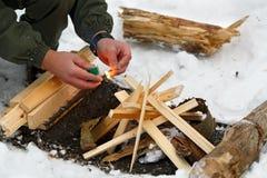 Un hombre pega un partido para hacer un fuego Imagen de archivo