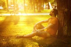 Un hombre pensativo feliz del soñador se está sentando en hierba verde en parque Foto de archivo