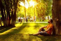 Un hombre pensativo feliz del soñador se está sentando en hierba verde en parque Imagen de archivo libre de regalías