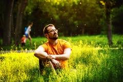 Un hombre pensativo serio se está sentando en hierba verde en un parque Imagenes de archivo