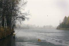 Un hombre pesca en la lluvia del otoño Fotos de archivo