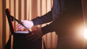 Un hombre pone el caso en una tabla, lo abre y mirando dentro almacen de metraje de vídeo