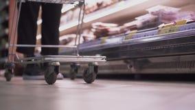 Un hombre pone productos en el carro que tira adentro del supermercado metrajes