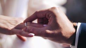 Un hombre pone su anillo de bodas de la mujer en su finger Primer muy bonito el momento de amor y de matrimonio metrajes