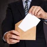 Un hombre pone una hoja de papel blanca en un sobre Imagen de archivo