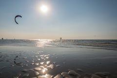 Un hombre practica kiteboarding con marea baja mientras que el sol fija Fotografía de archivo