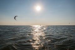 Un hombre practica kiteboarding con marea baja mientras que el sol fija Imagen de archivo