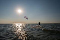 Un hombre practica kiteboarding con marea baja mientras que el sol fija Imagenes de archivo