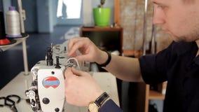 Un hombre prepara una máquina de coser para trabajar almacen de metraje de vídeo