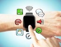 Un hombre presiona el reloj digital con los medios iconos sociales Foto de archivo libre de regalías