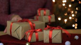Un hombre puso las cajas de regalo de la Navidad en la tabla con el fondo de las luces del bokeh metrajes