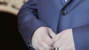 Un hombre que abotona un botón en una chaqueta azul elegante almacen de metraje de vídeo