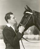 Un hombre que acaricia su caballo Imagen de archivo libre de regalías