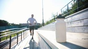 Un hombre que activa en las tribunas y las tomas una botella de agua almacen de metraje de vídeo