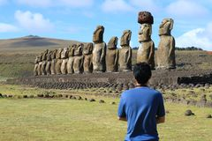 Un hombre que admira las estatuas enormes de Moai de Ahu Tongariki, isla de pascua fotos de archivo