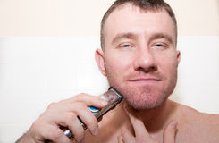 Un hombre que afeita su cara Fotos de archivo