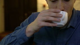 Un hombre que bebe té o el café durante el trabajo almacen de metraje de vídeo