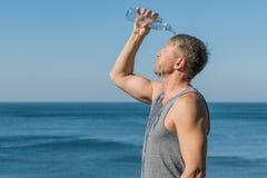 Un hombre que bebe y vierte el agua en su cara de la botella en el océano, restaurando después de un entrenamiento imagenes de archivo