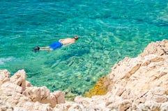 Un hombre que bucea en un mar o un océano azul del claro del crytsla por el rocho Foto de archivo
