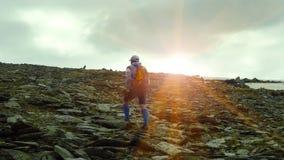 Un hombre que camina con los polos en un paisaje de la montaña por la mañana en el amanecer Los rayos del sol miran hacia fuera d imagen de archivo