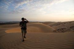 Un hombre que camina en la duna de arena Imágenes de archivo libres de regalías