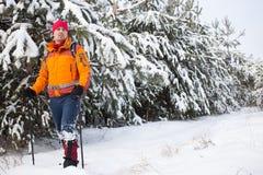 Un hombre que camina en la nieve con una mochila imagenes de archivo
