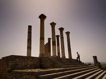 Un hombre que camina en las ruinas romanas de Volubilis. Foto de archivo