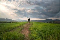 Un hombre que camina solamente en el camino con el cielo dramático Fotos de archivo libres de regalías