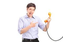 Un hombre que celebra un teléfono y gesticular Fotos de archivo libres de regalías