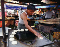 Un hombre que cocina las tortas en la calle en Mandalay, Myanmar Foto de archivo libre de regalías