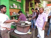 Un hombre que cocina los chapatis Fotos de archivo