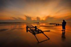 Un hombre que coloca la playa cercana y que disfruta de puesta del sol Imagenes de archivo