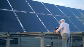 Un hombre que comprueba los paneles solares Los ingenieros miran las baterías del sol y las tocan almacen de video