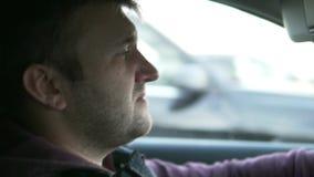 Un hombre que conduce un coche Cámara lenta almacen de metraje de vídeo
