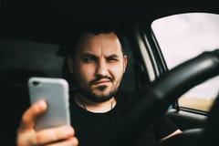 Un hombre que conduce un coche distraído por un smartphone imagen de archivo