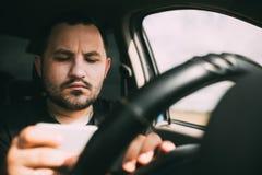 Un hombre que conduce un coche distraído por un smartphone fotos de archivo libres de regalías