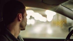 Un hombre que conduce el coche y que habla en el teléfono móvil almacen de video