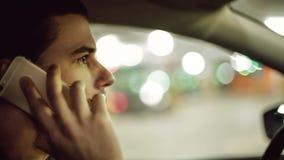 Un hombre que conduce el coche y que habla en el teléfono móvil metrajes