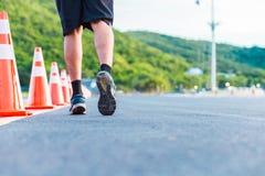 Un hombre que corre en el camino y la monta?a detr?s imagen de archivo libre de regalías