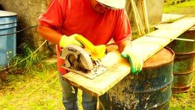 Un hombre que corta un pedazo de madera metrajes