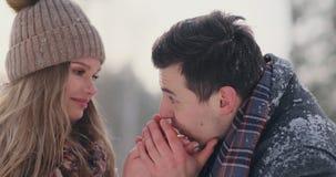 Un hombre que cuida se calienta las manos del ` s de la esposa en el invierno en la calle en un parque nevado almacen de video