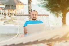 Un hombre que descansa en un país exótico y que trabaja remotamente en su l imágenes de archivo libres de regalías