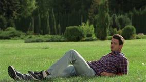 Un hombre que disfruta de un resto en la hierba almacen de video