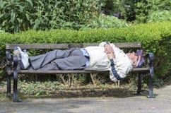Un hombre que duerme en el parque Fotografía de archivo