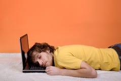 Un hombre que duerme en la computadora portátil imagen de archivo libre de regalías