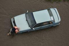 Un hombre que empuja su coche con el motor atascado en agua Foto de archivo libre de regalías