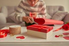 Un hombre que envuelve los regalos en cinta roja y rosas frescas valentines imagenes de archivo